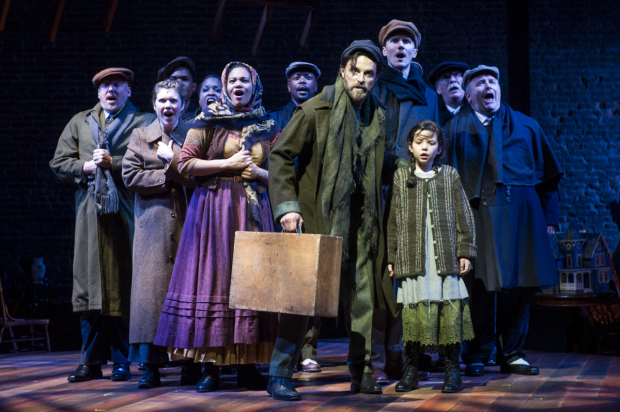 Tateh (J. Anthony Crane) and his daughter (Frances Evans) with fellow immigrants coming to America in Ragtime.