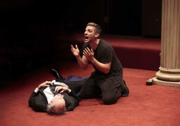 Oscaar Isaac as Hamlet kneels above Peter Friedman as Polonius.