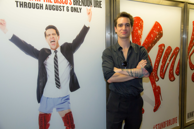 Panic! At the Disco's Brendon Urie stands next to his subway ad for Kinky Boots.