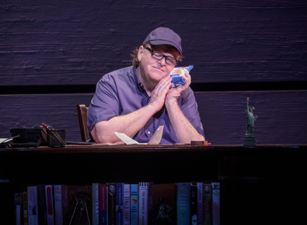 Michael Moore cradles a bag of Ruffles in The Terms of My Surrender on Broadway.  Michael Moore