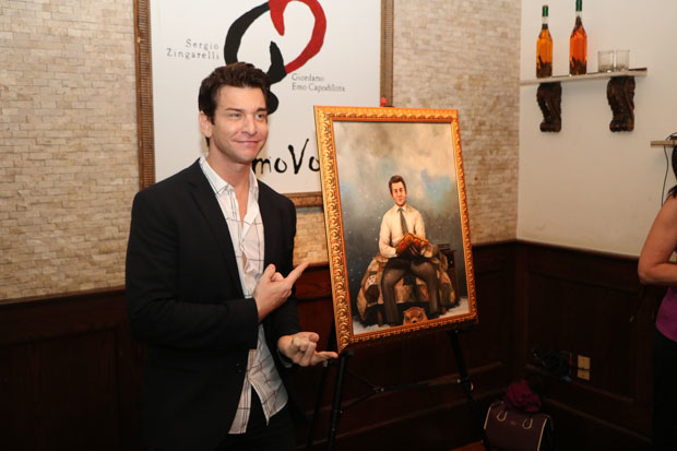 Andy Karl poses next to the painting of him unveiled at Tony di Napoli Restaurant.