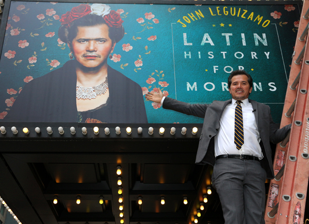 John Leguizamo hops on a ladder to pose with his Broadway marquee.