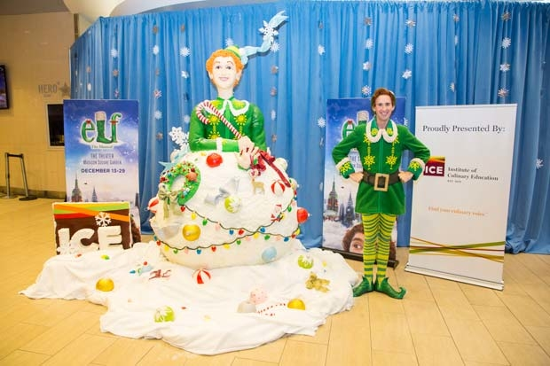 Buddy the Elf stands next to his likeness, a towering statue of Rice Krispies Treats.