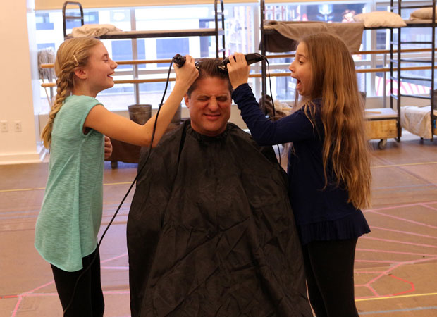 Christopher Sieber (center) gets a haircut from Cassidy Pry and Peyton Ella for his role as Oliver Warbucks in Annie, directed by Mark S. Hoebee, at Paper Mill Playhouse.