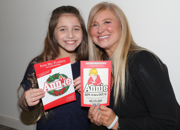 Peyton Ella and Tara Kennedy show off brochures from their respective productions of Annie at Paper Mill Playhouse.