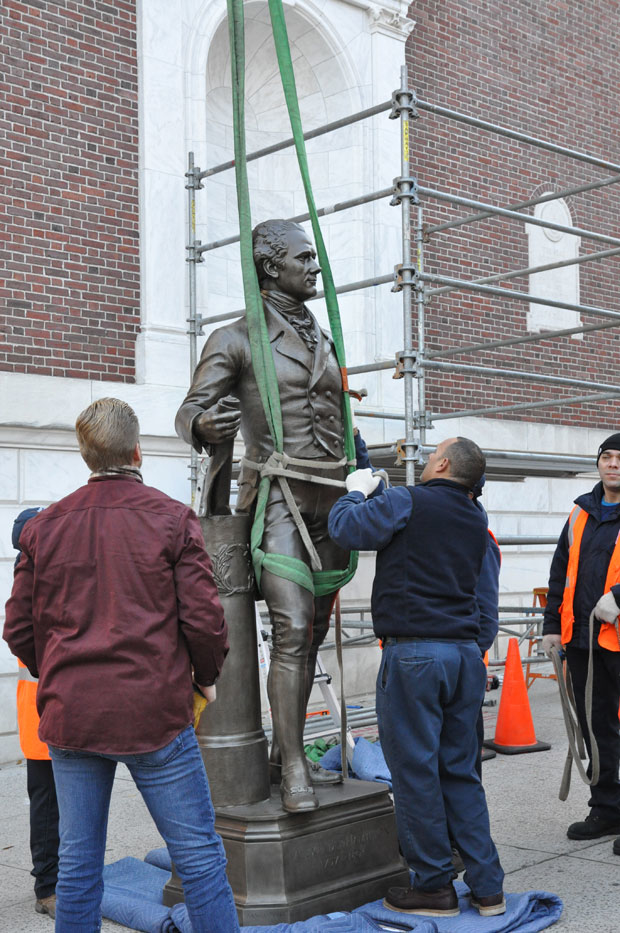 The statue of Alexander Hamilton is made ready to be lifted back into place.
