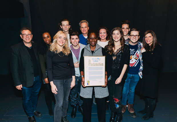 The company of Dear Evan Hansen grab a photo with their proclamation from the Mayor's Office.