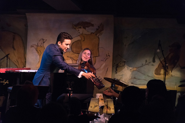 John Lloyd Young hands a copy of the Jersey Boys DVD to an audience member as violinist Gokce Erem looks on.