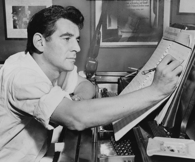A young Leonard Bernstein annotates a score at the piano.