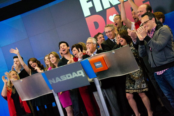 The cast and creative team of First Date ring the Nasdaq closing bell.
