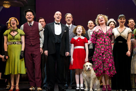 The principal cast members of Annie — Kirsten Wyatt, Clarke Thorell, Anthony Warlow, Taylor Richardson, Sunny, Faith Prince, and Brynn O'Malley — sing the show's finale song onstage at the Palace Theatre.