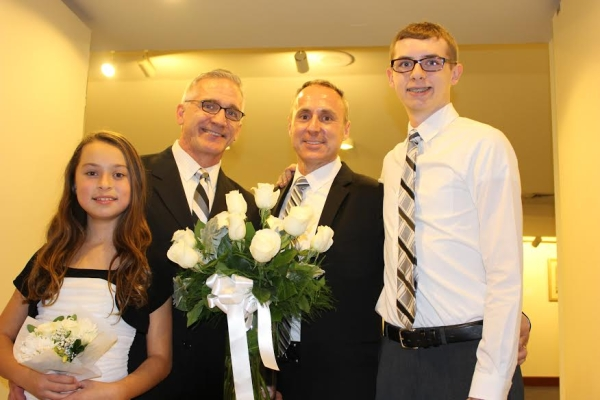 Paper Mill Playhouse Artistic Director Mark S. Hoebee (second from left) with husband Larry Elardo at their wedding, with children Ashley and Stephen.