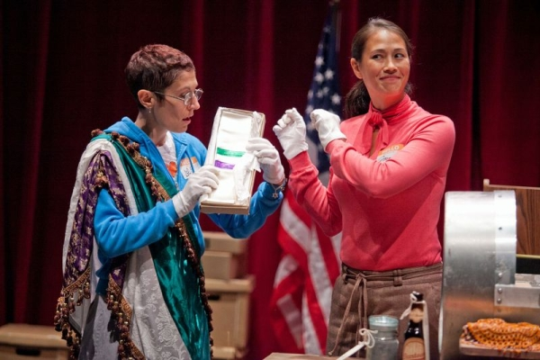 Rachel Grossman and Elaine Yuko Qualter show off an artifact from the Beertown Time Capsule in dog and pony dc's Beertown at 59E59 Theaters.