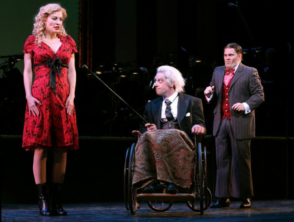 "Belle Schlumpfert (Rachel York) asks miserly banker Amos Pinchley (Christian Borle) to dig ""Deep Down Inside"" for his hidden niceness. His son Junior (Robert Creighton) looks on incredulously in the Encores! production of Little Me at New York City Center."