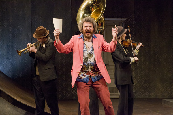 Sir Toby Belch (James Sugg) is flanked by a Balkan brass band in Pig Iron Theatre Company's production of Twelfth Night at Abrons Arts Center.