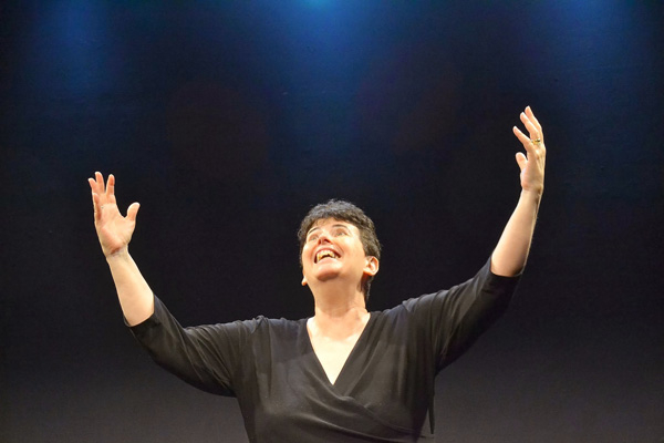 Monica Bauer conducts an imaginary symphony orchestra in her autobiographical solo show The Year I Was Gifted, directed by Carolyn Ladd at Stage Left Studio.
