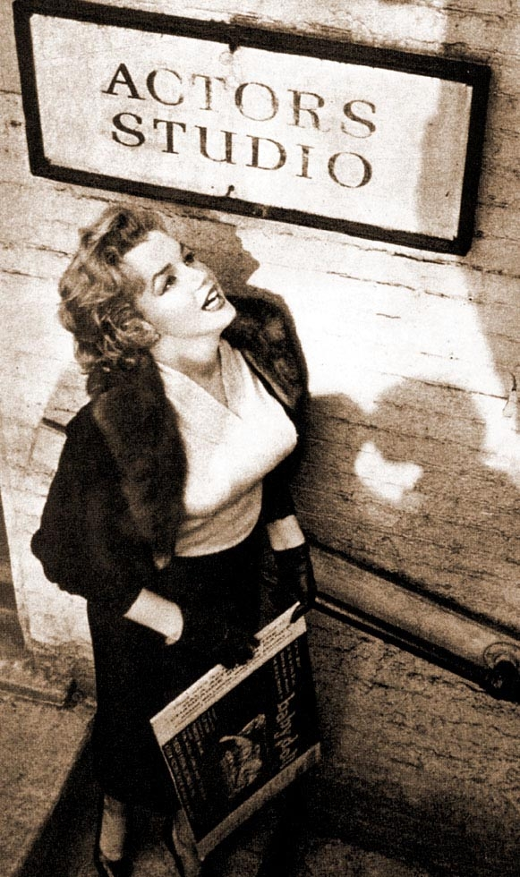 Marilyn Monroe outside stands beneath the Actor's Studio sign in 1956.