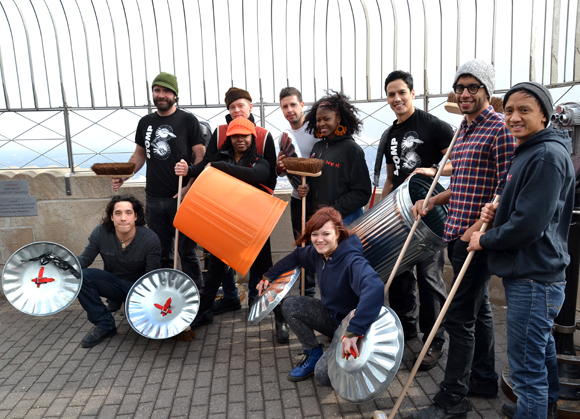 The cast members of Stomp pose with their legendary percussion instruments at the top of the Empire State Building.