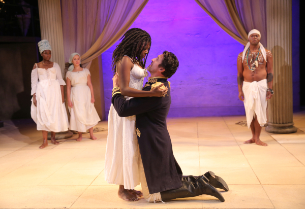 Antony (Jonathan Cake) is brought to his knees by Cleopatra (Jaoquina Kalukango) as the Soothsayer (Chivas Michael) looks on knowingly in Shakespeare's Antony and Cleopatra at the Public Theater, directed by Tarell Alvin McCraney.