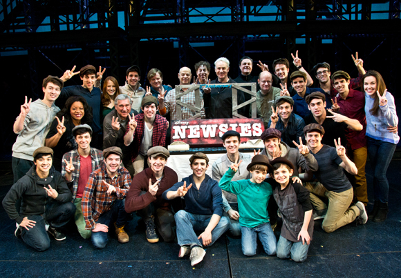 The current Broadway cast of Newsies poses with its specially designed cake from City Bakery.