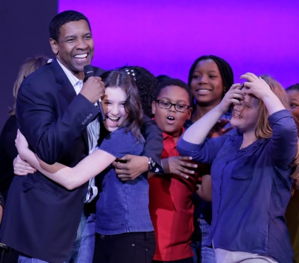 Denzel Washington gets a big hug from participating students in the Broadway Junior Student Share celebration on May 19.