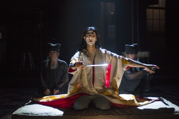 Sean Fortunato as Rene Gallimard, flanked by Greek chorus members Sarah Lo and Aurora Adachi Winter in M. Butterfly, directed by Charles Newell, at Chicago's Court Theatre.