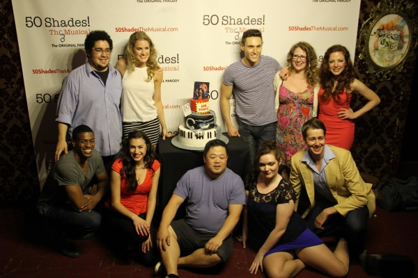 The cast of 50 Shades! The Musical poses with the show's celebratory cake.