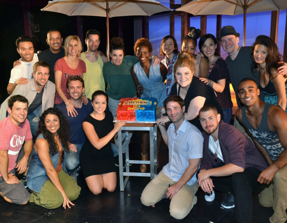 Idina Menzel (center) and the cast of If/Then show off their 100th performance cake.