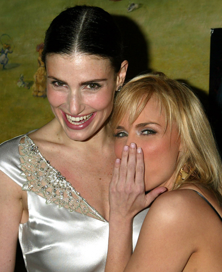 Idina Menzel and Kristin Chenoweth recreate the famous Wicked logo artwork at the musical's Broadway opening-night party in 2003.