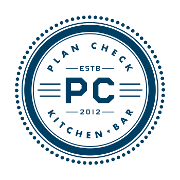 This is the restaurant logo for Plan Check Kitchen + Bar