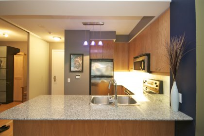 Designer Kitchen Cabinetry With Stainless Steel Appliances, Granite Counter Tops, Valance Lighting & A Breakfast Bar.