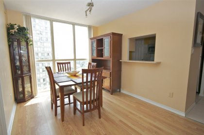 Bright Open Concept Dining Area With Floor-To-Ceiling Windows & Laminate Flooring Throughout.