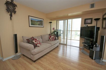 Bright Open Concept Living Area With Floor-To-Ceiling Windows & Laminate Flooring Throughout.