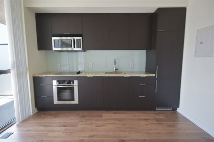 Designer Kitchen Cabinetry With Stainless Steel Appliances, Flat Top Stove, Marble Counter Top & Undermount Sink.