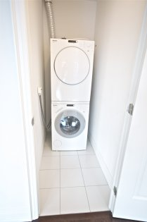 Stacked Miele Washer & Dryer With Ample Storage Area.