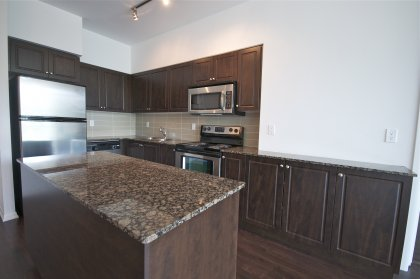 Designer Kitchen Cabinetry With Stainless Steel Appliances, Granite Counter Tops, Hardwood Flooring & A Centre Island.