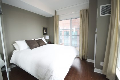 Spacious Sized Bedroom With Mirrored Closets & A Private Walk-Out Balcony Facing Lake Views.