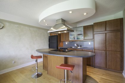 Designer Kitchen Cabinetry With Valance Lighting, Pot Lights, Flat Top Stove & A Breakfast Bar.