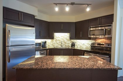 Designer Kitchen Cabinetry With New Stainless Steel Appliances, Granite Counter Tops, Stone Backsplash & A Centre Island.