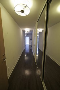 Suite Entrance With Gleaming Hardwood Flooring & Large Mirrored Closets.