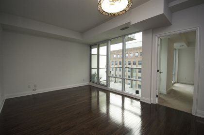 Bright Floor-To-Ceiling Windows With Gleaming Hardwood Flooring.