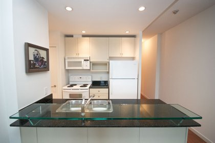 Designer Kitchen Cabinetry With Granite Counter Tops, Pot Lighting & A Glass Breakfast Bar.