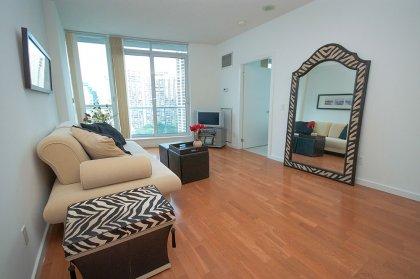 Bright Floor-To-Ceiling Windows Onlooking City & Lake Views With Hardwood Flooring.