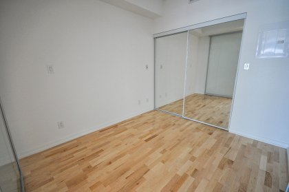 Spacious Sized Bedroom With Hardwood Flooring, Mirrored Closet & Sliding Doors.