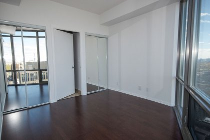 Master Bedroom With Mirrored Closets & Hardwood Flooring Facing Unobstructed Views.