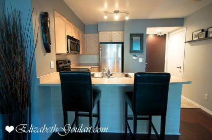 Designer Kitchen Cabinetry With Stainless Steel Appliances, Ceramic Backsplash & A Breakfast Bar.