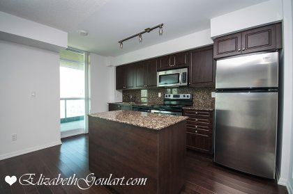 Designer Kitchen Cabinetry With Stainless Steel Appliances & Granite Counter Tops & Hardwood Flooring.