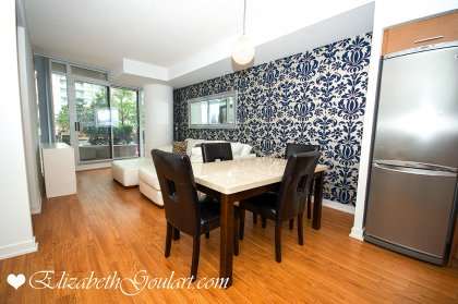 Open Concept Dining / Living Areas With Floor-To-Ceiling Windows & Laminate Flooring.