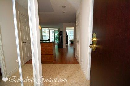Suite Foyer With Granite Flooring & Mirrored Closets.