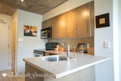 Designer Kitchen Cabinetry With Stainless Steel Appliances, Lime Stone Counter Tops, Undermount Sink, Glass Tile Backsplash & A Breakfast Bar.